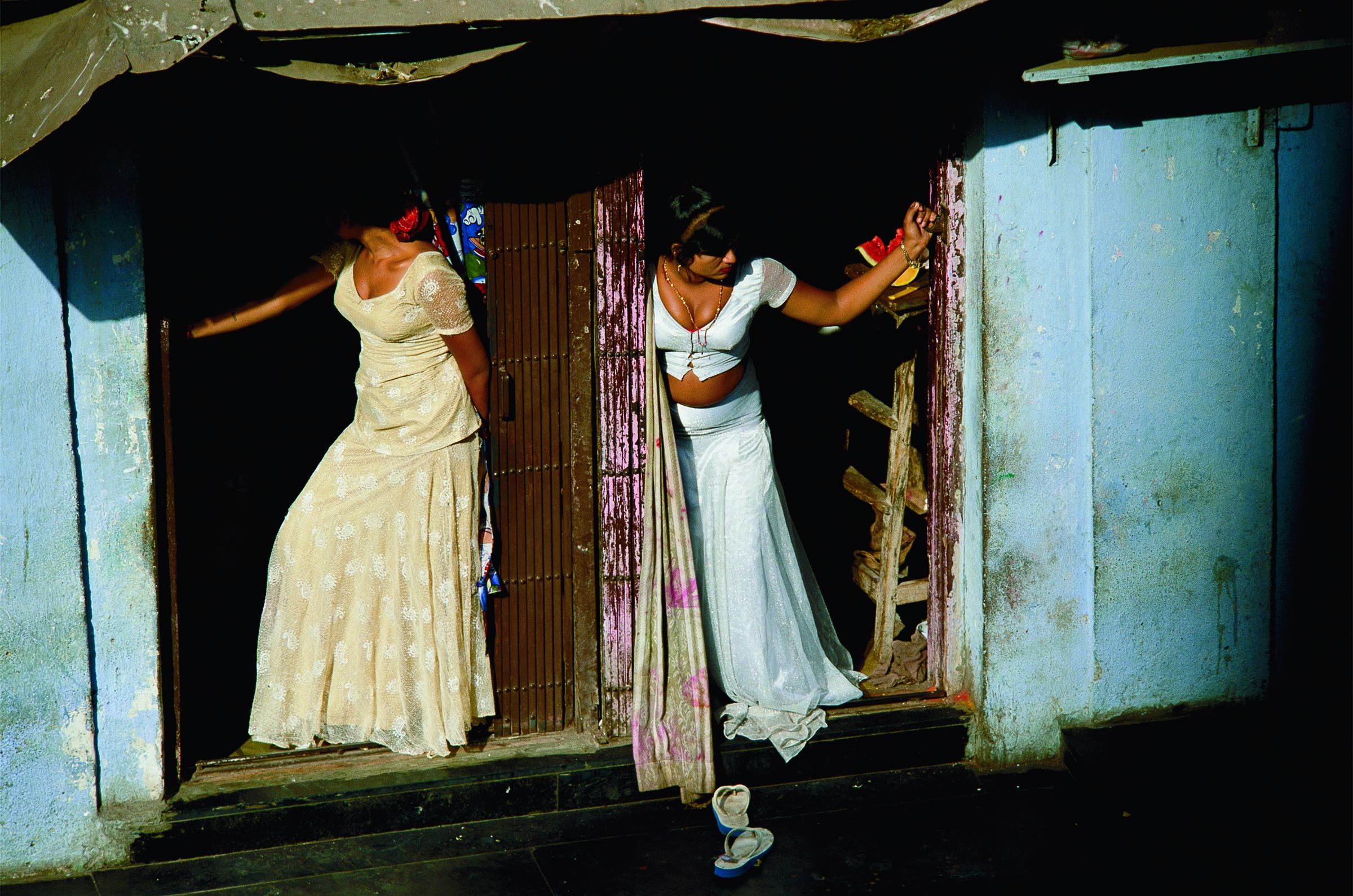 """Prostitutas, são conhecidas como meninas engaioladas são, muitas vezes, escravas sexuais, exibem-se em uma rua de Mumbai. Foto de Jodi Cobb, cortesia da National Geographic """"Mulheres de Visão""""."""