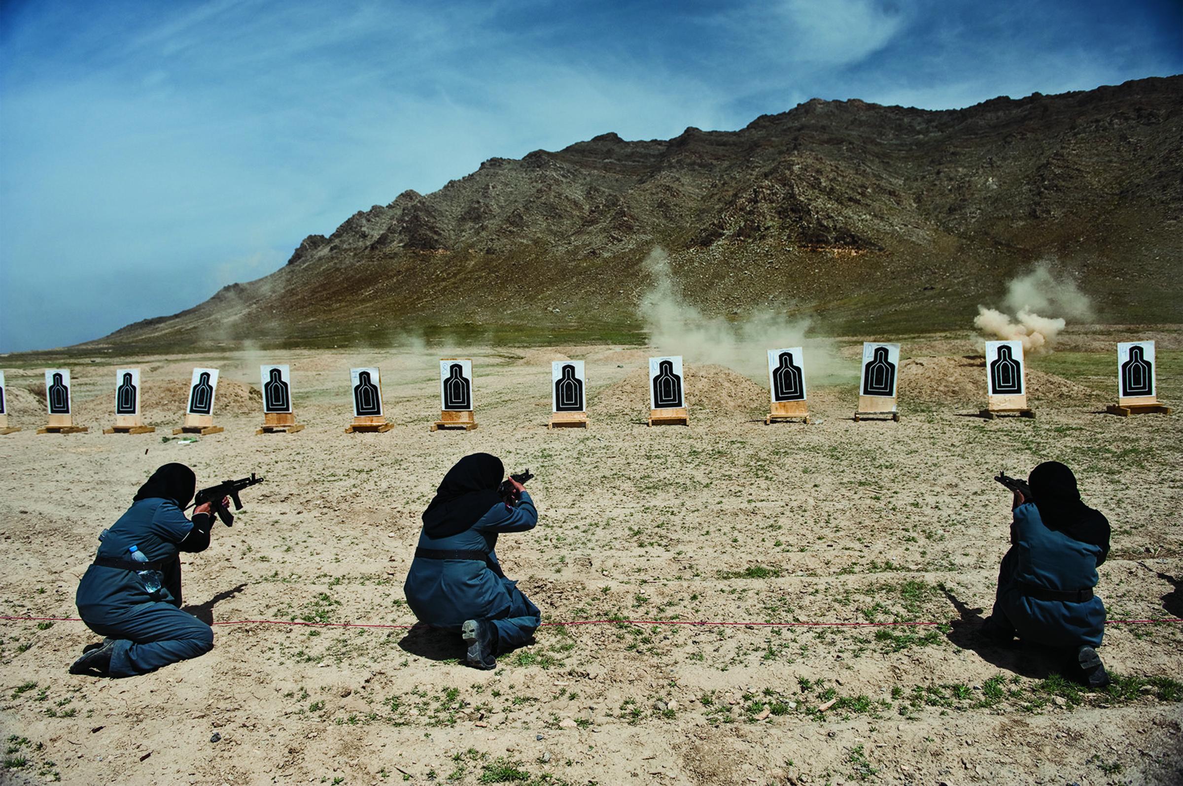 """Mulheres - principalmente viúvas - treinam para realizar trabalhos policiais em um campo de tiro perto de Cabul. Foto de Lynsey Addario, cortesia da National Geographic """"Mulheres de Visão""""."""