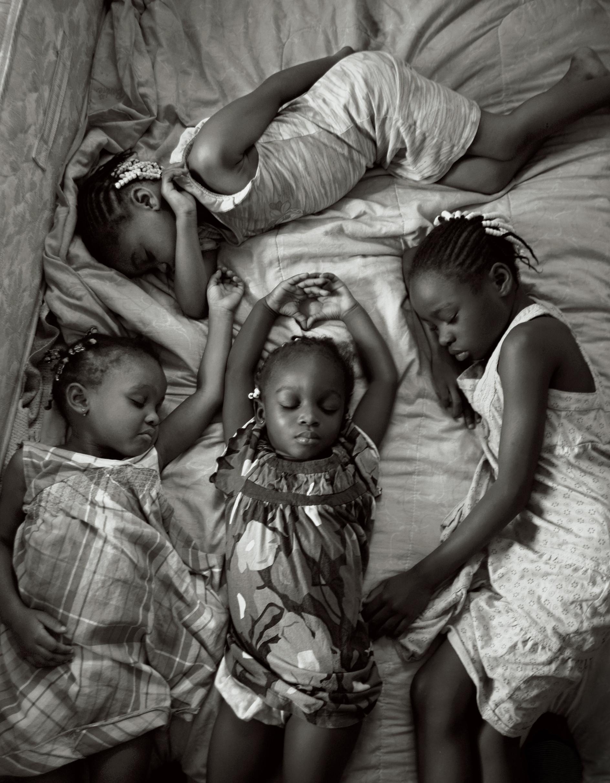 """Quatro jovens irmãs tiram uma soneca, em uma tarde de domingo, em uma cama, em Miami, na Florida, depois de frequentar a igreja. Foto de Maggie Steber, cortesia da National Geographic """"Mulheres de Visão""""."""