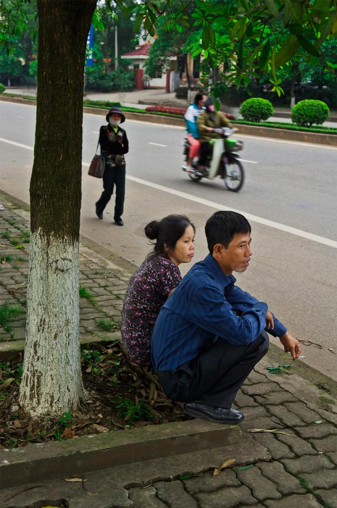 Nguyen Quoc Khanh sits with his wife (?) under a tree in Viet Tri, Vietnam. 2008